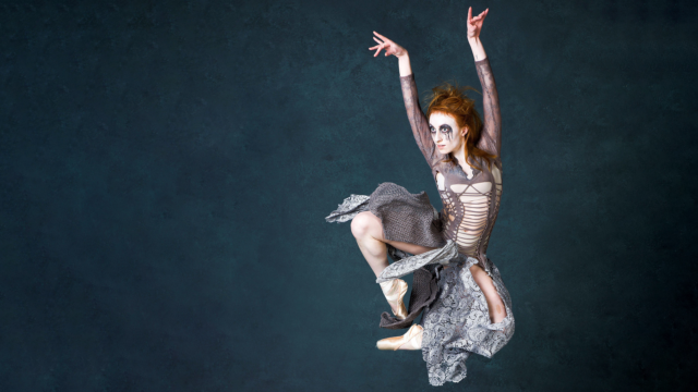 A ballet dancer with red hair leaps off the ground
