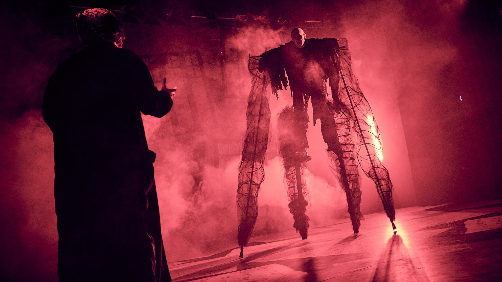 Christmas Carol production shot: An actor on stilts creates a look of a large ghostly monster. Smoke and red lighting fills the image