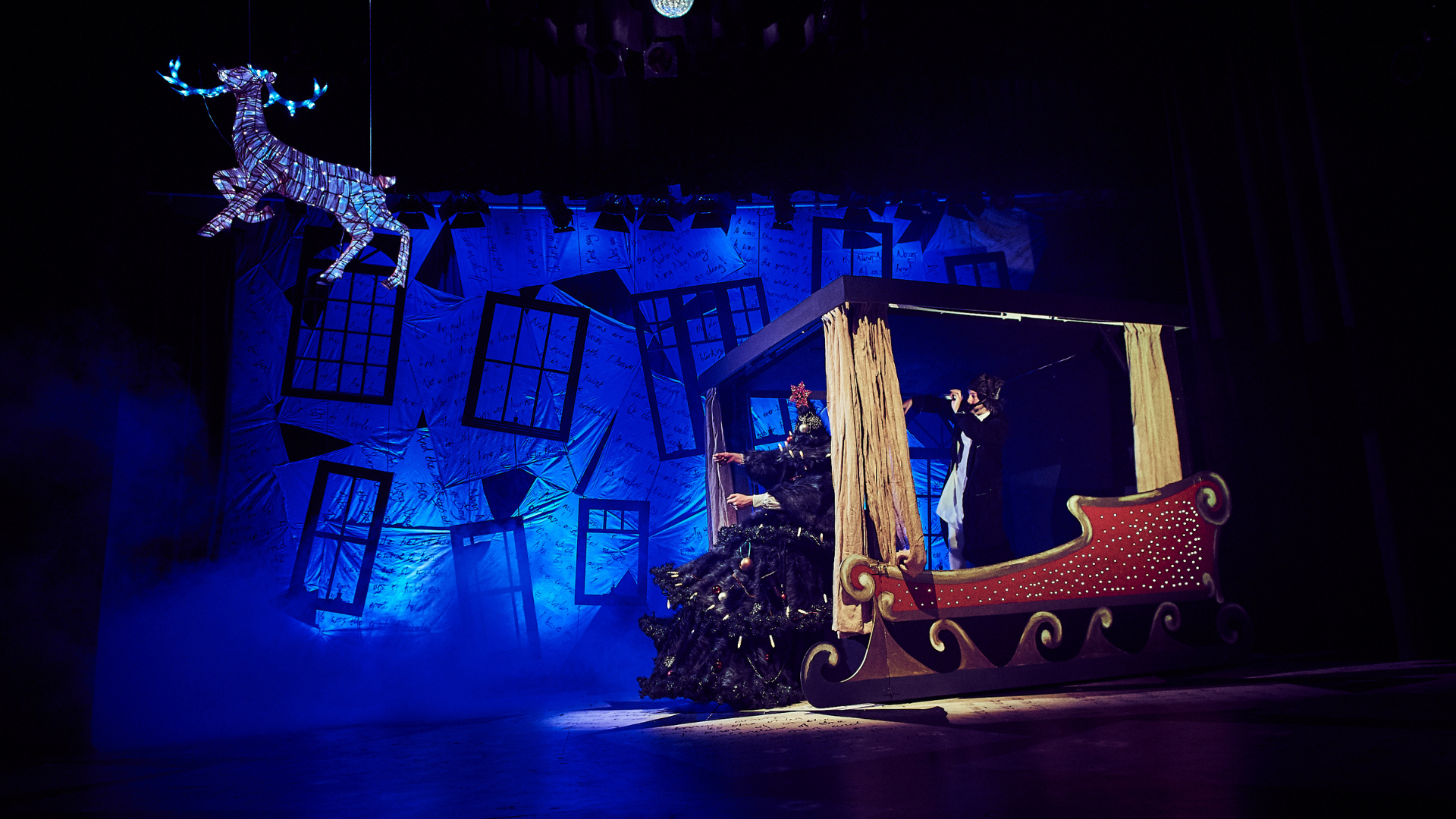 A Christmas Carol production shot: on stage there is a large sleigh with a Christmas tree. In the air there is a reindeer covered in lights