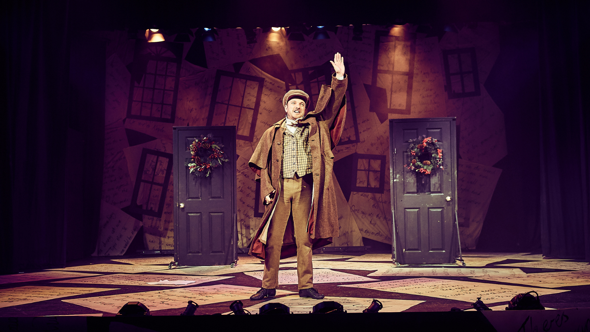A Christmas Carol production shot: a character is stood in the centre waving at the audience. In the background, there are 2 doors decorated with Christmas wreaths