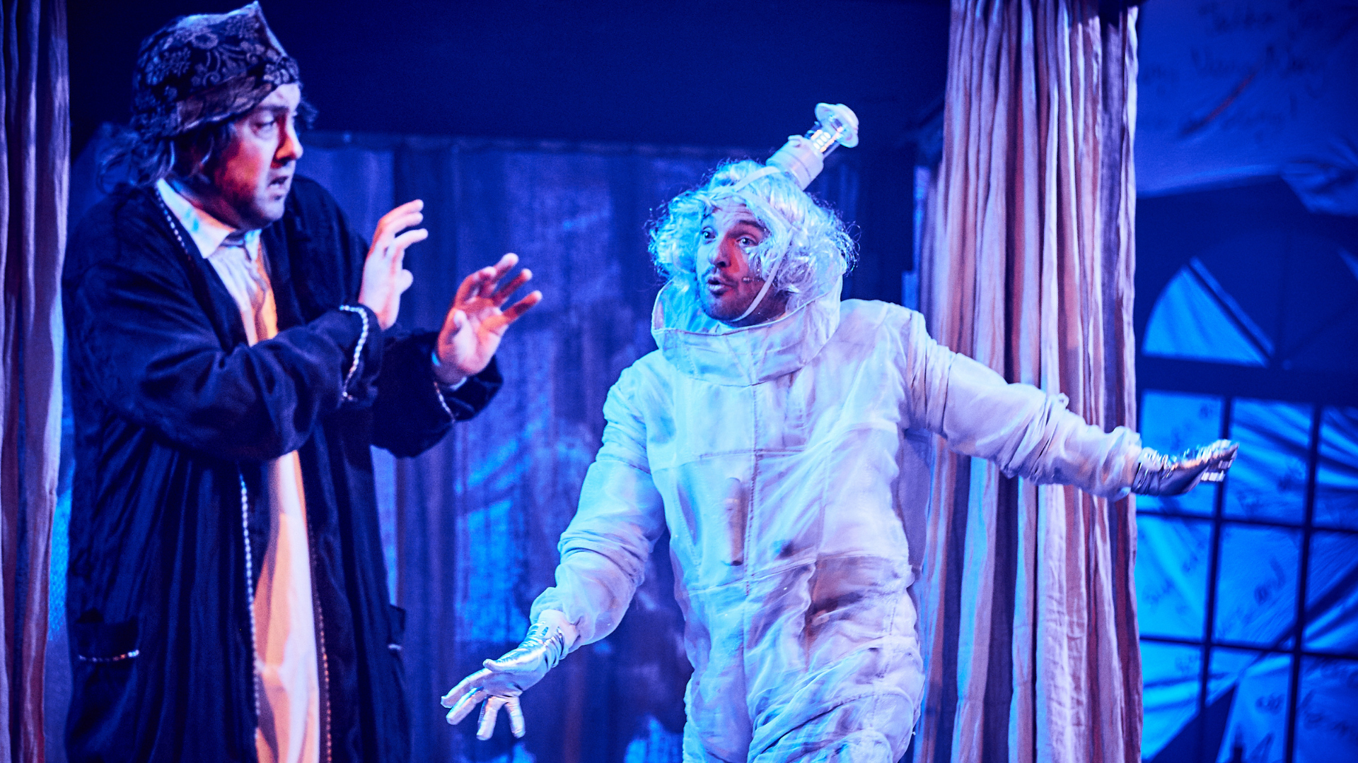 A Christmas Carol production shot: Scrooge looks scared of one of the Christmas ghosts