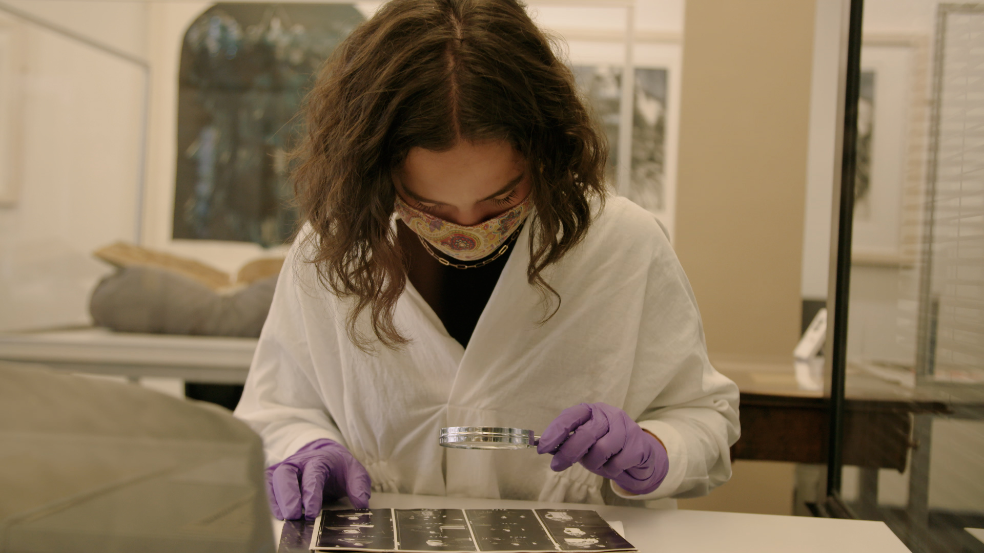 A female intern dressed in a lab coat, gloves and goggles uses a magnifying glass to look at photo negatives in the archive
