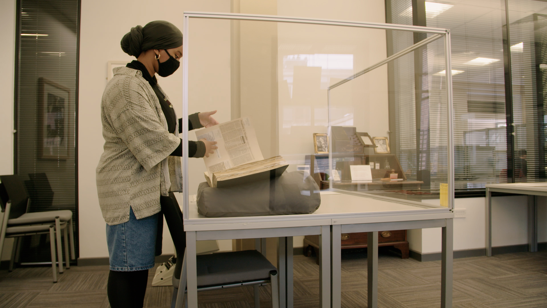 A female intern dressed in a lab coat and gloves inspects a book in the archive