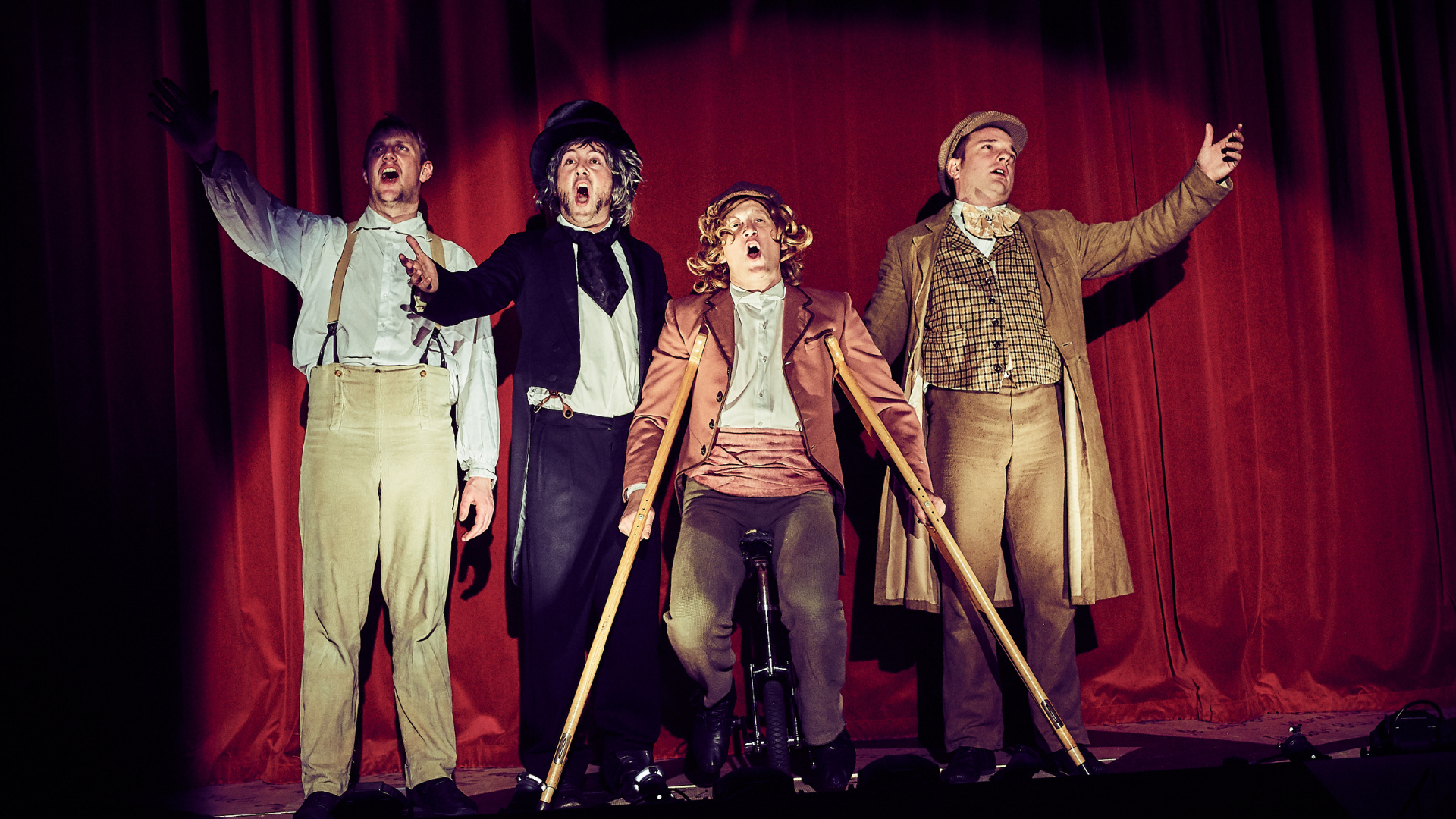 A Christmas Carol production shot: 4 character stood in front of the curtain singing. 1 character is on crutches.