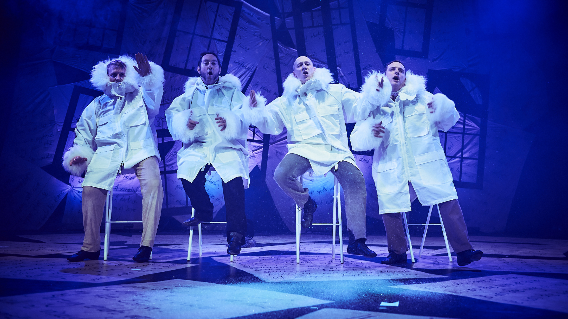 A Christmas Carol production shot: 4 characters sat on stool, wearing large white winter coats