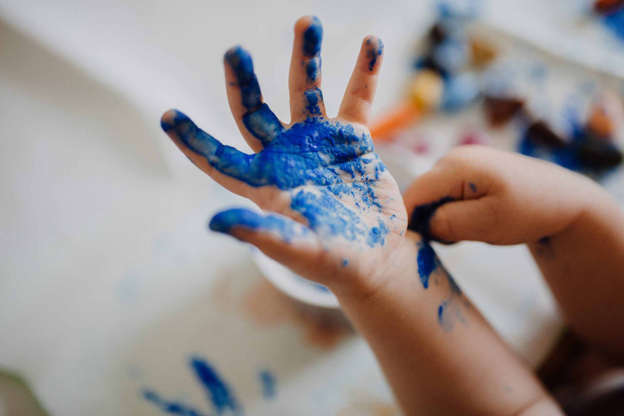 A child's hand covered in paint
