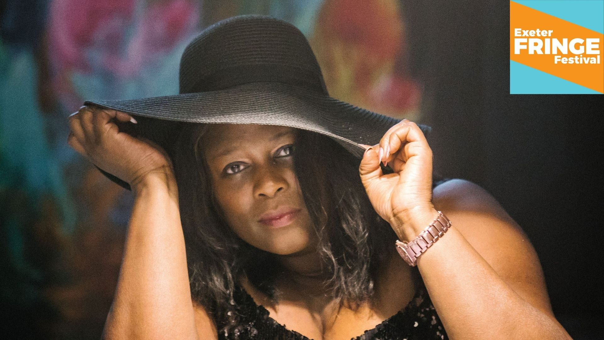 Promotional image featuring Annette Gregory with a wide-rimmed black sun hat
