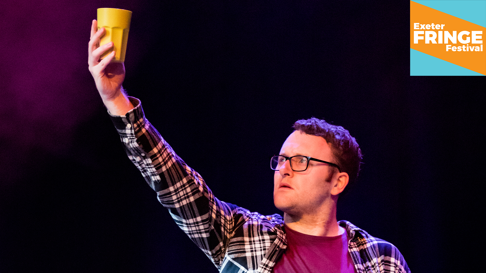 Promotional image for Futures Scratch Night - a young man on stage, holding high a yellow cup
